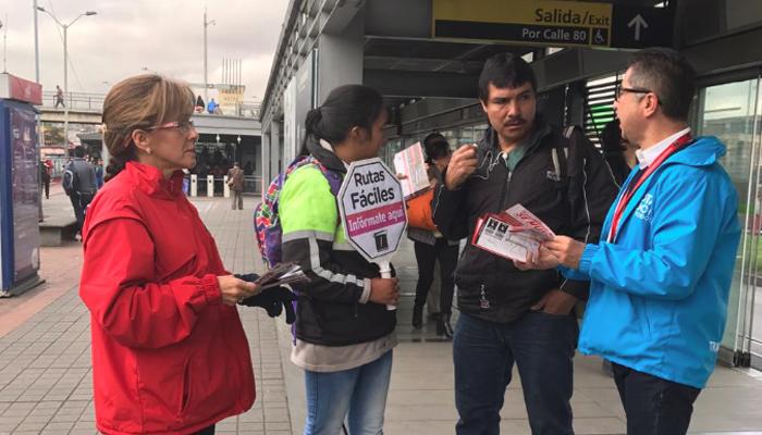Dos funcionarios de TransMilenio explicándole a un señor en una estación, la ruta fácil que pude tomar