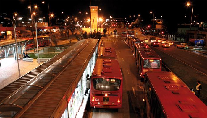 TransMilenio llegando a una estación en las horas de la noche
