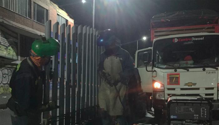 Imagen donde dos personas están soldando los cerramientos perimetrales en  una estación