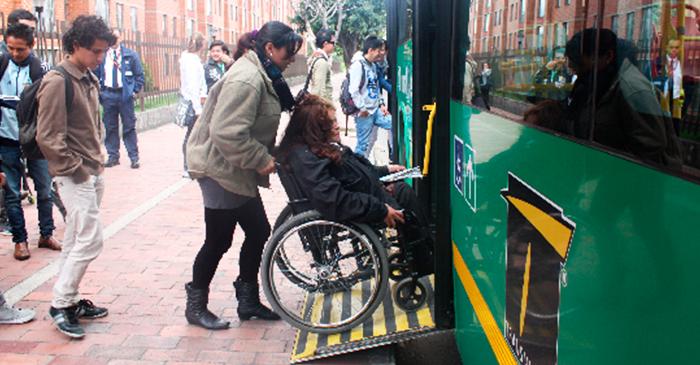 Persona ayudando a una persona en silla de rueda a subir por la plataforma  de un alimentador