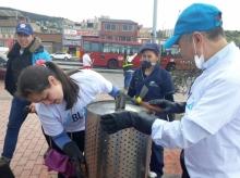 Subgerente General limpiando  caneca de basura en el sector de San Cristobal