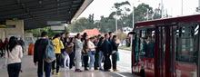 Usuarios esperando  la llegada de un bus de TransMilenio en un  portal del Sistema